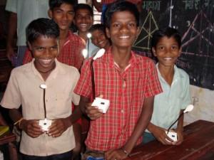 Jungen mit Lampen - Schüler einer Grundschule im Hinterland von Bombay haben neue Solar-Lampen für ihre Hausaufgaben erhalten